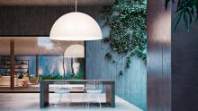 FontanaArte: Avico suspension lamp in outdoor setting above table.